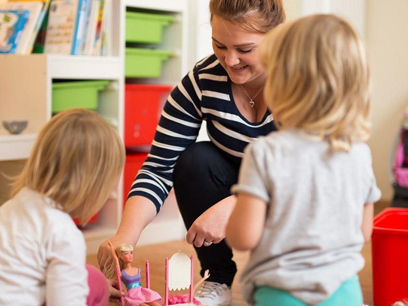 Kinder spielen mit Betreuerin