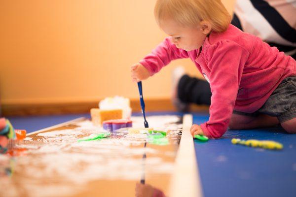 Kleinkind malt mit Pinsel und Farben