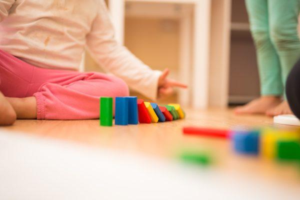 Kinde spielt mit Bauklötzen auf dem Boden
